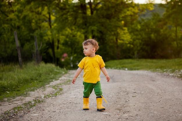 Um menino de fazenda pequena andando por uma estrada de terra.