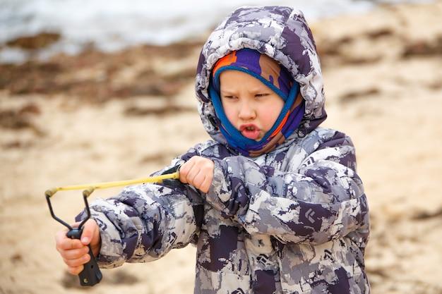 Um menino de jaqueta na areia atira com um estilingue