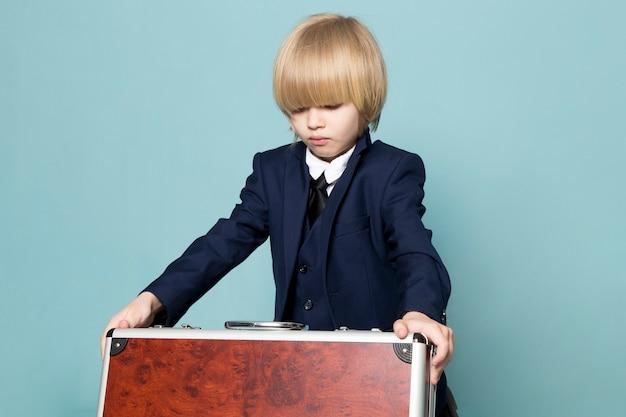 Um menino de negócios bonito vista frontal no terno clássico azul posando segurando segurando a mala marrom-prata negócios trabalho moda