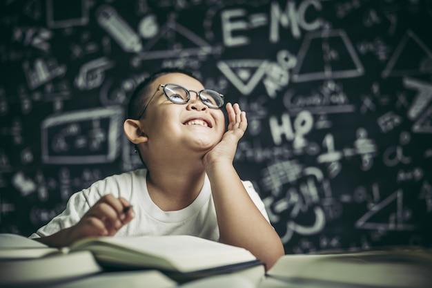 Um menino de óculos escrevendo na sala de aula