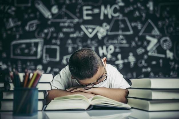 Um menino de óculos estudando e sonolento.