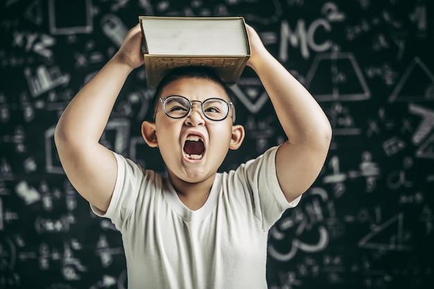 Um menino de óculos estudou e colocou um livro na cabeça na sala de aula.