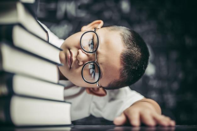 Um menino de óculos sentado na sala de aula contando livros