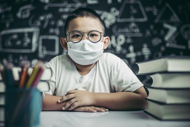 Um menino de óculos sentado na sala de aula estudando