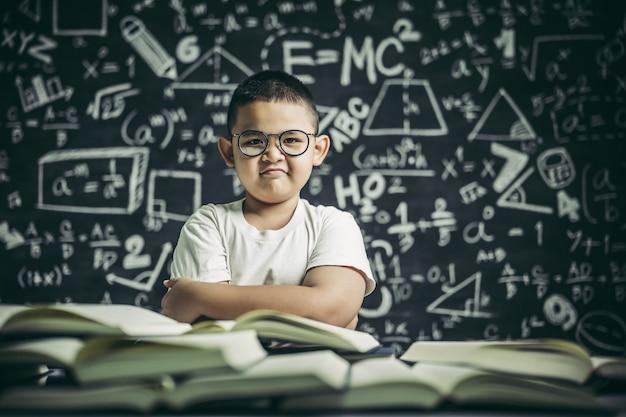 Um menino de óculos sentado na sala de aula lendo