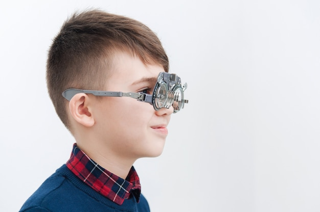 Um menino de óculos verifica a visão do olho em um oftalmologista
