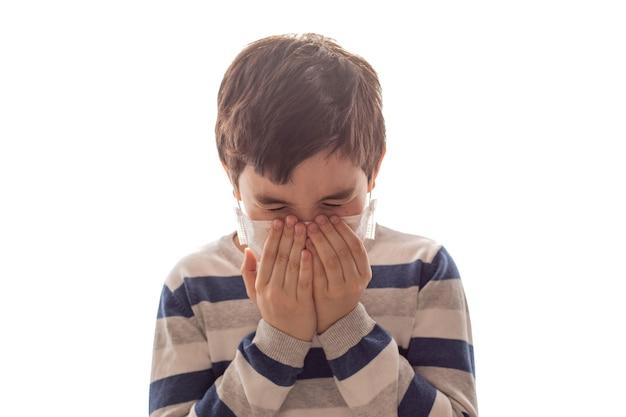 Um menino de olhos fechados espirra ou tosse com as mãos no branco