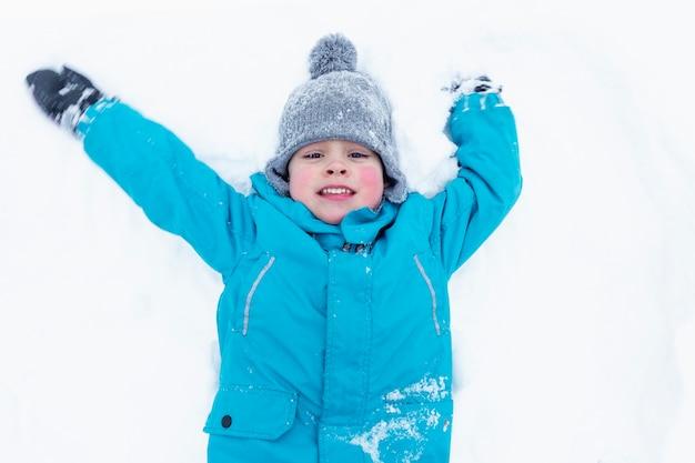 Um menino de paletó azul está deitado na neve e ri. jogos ao ar livre. vista do topo.