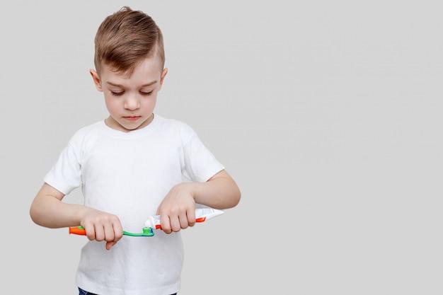 Um menino de seis anos aperta a pasta de dentes na escova de dentes