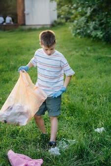 Um menino de sete anos ao pôr do sol está empenhado na coleta de lixo no parque. cuidado com o meio ambiente, reciclagem.