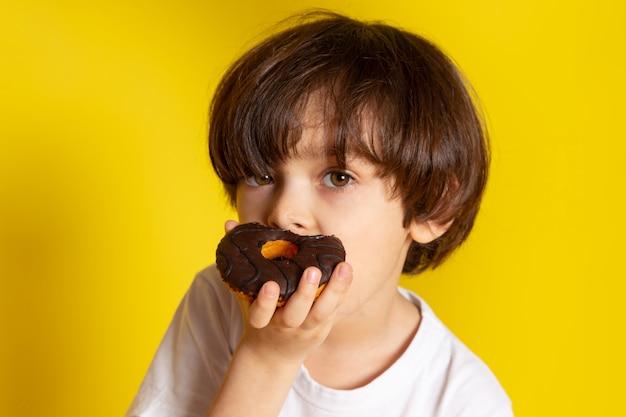 Um menino de vista frontal comendo rosquinhas de chocolate em camiseta branca no chão amarelo
