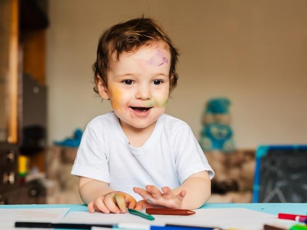Um menino desenha com marcadores coloridos em um pedaço de papel