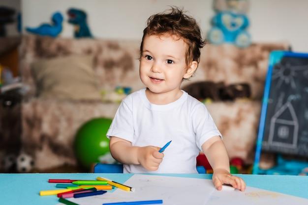 Um menino desenha em folhas de papel sobre a mesa com lápis de cor