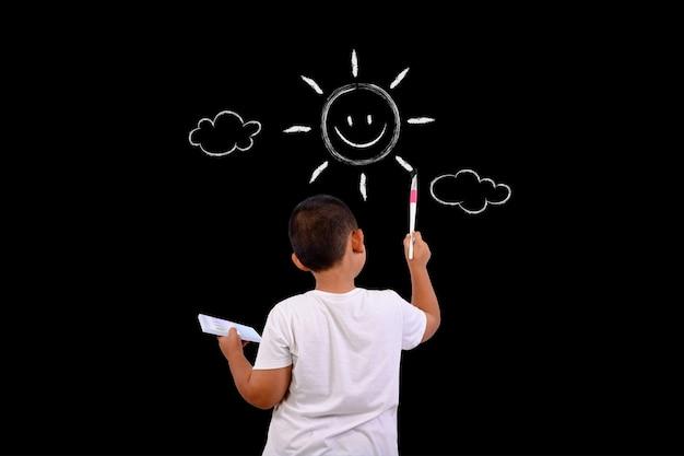 Um menino desenha o céu e o sol com uma lousa