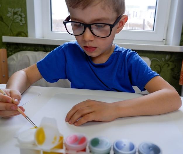 Um menino desenha o sol com tintas em uma folha de papel branca sentada à mesa. Foto Premium