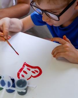 Um menino desenha um coração vermelho em um papel branco com um pincel e tintas