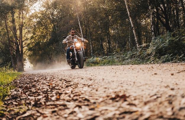 Um menino dirigir uma moto na estrada de pedra