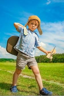 Um menino do avião brinca com a natureza no parque. menino no piloto de férias.