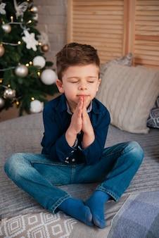 Um menino doce está sentado com os olhos fechados perto da árvore de ano novo e faz um pedido, cruzando as mãos perto do peito