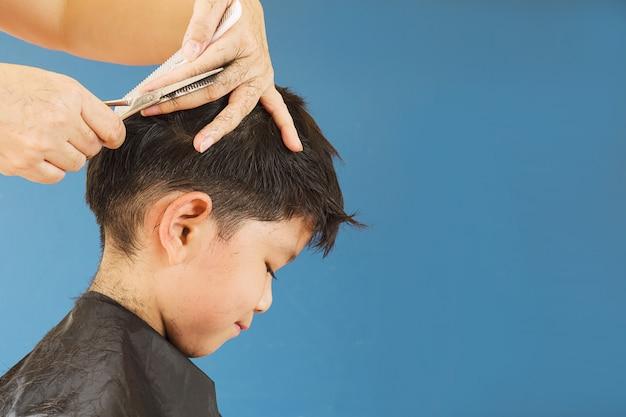 Um menino é cortado o cabelo pelo cabeleireiro
