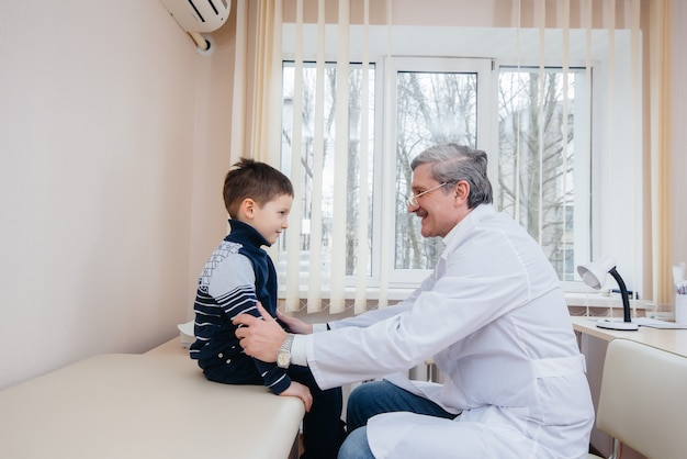 Um menino é ouvido e tratado por um médico experiente em uma clínica moderna. um vírus e uma epidemia