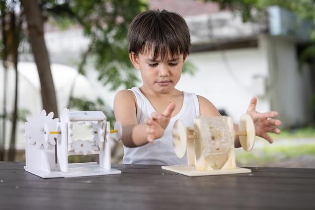 Um menino e preste atenção ao aprender o modelo de robô de mecanismo de simulação de madeira na mesa em casa