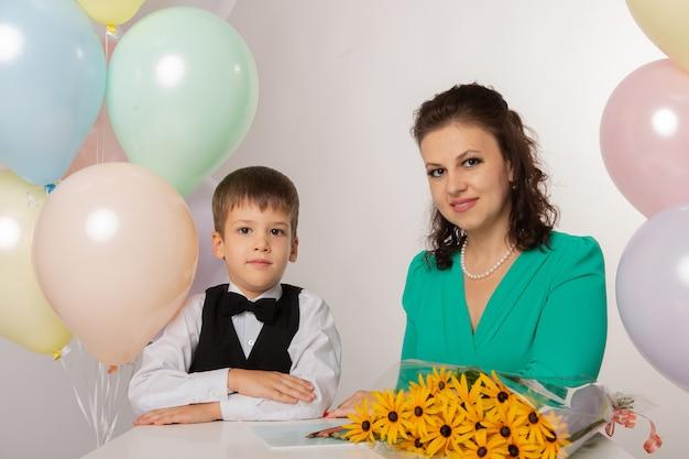 Um menino é um aluno da primeira série em um fundo branco com sua mãe com bolas e flores