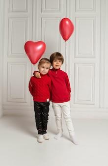 Um menino e uma menina abraçam e seguram balões vermelhos em forma de coração em branco