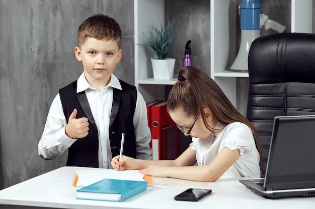 Um menino e uma menina amigáveis posam como trabalhadores de escritório em uma mesa branca no escritório