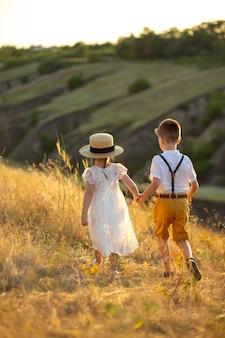 Um menino e uma menina andam de mãos dadas. menina segurando a mão do menino lindo casal lindos filhos de mãos dadas