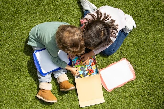 Um menino e uma menina brincam com as letras do alfabeto no jardim. escola em casa.