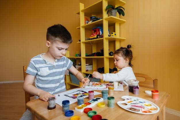 Um menino e uma menina brincam juntos e pintam. recreação e entretenimento