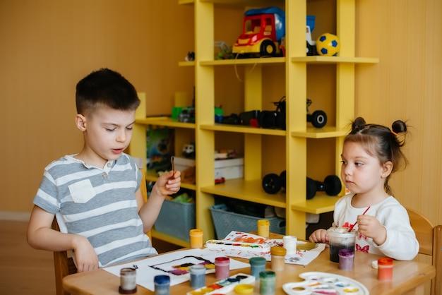 Um menino e uma menina brincam juntos e pintam
