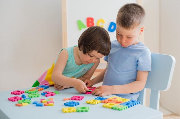 Um menino e uma menina coletar um quebra-cabeça macia na mesa