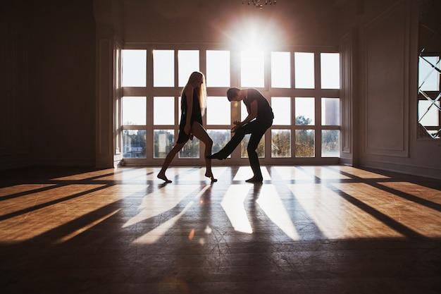 Um menino e uma menina com longos cabelos loiros em pé na frente da janela. dançarinos durante um treino. problemas e dificuldades nas relações. a situação difícil da vida. fotografia conceitual