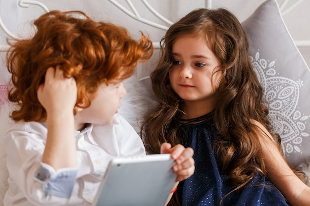 Um menino e uma menina deitar na cama e jogar