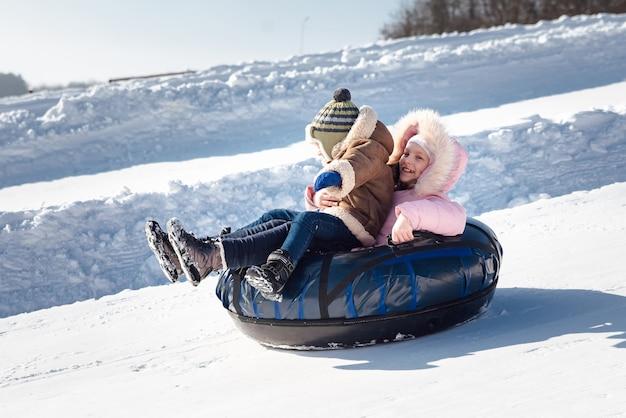 Um menino e uma menina descem de bóia em um tubo