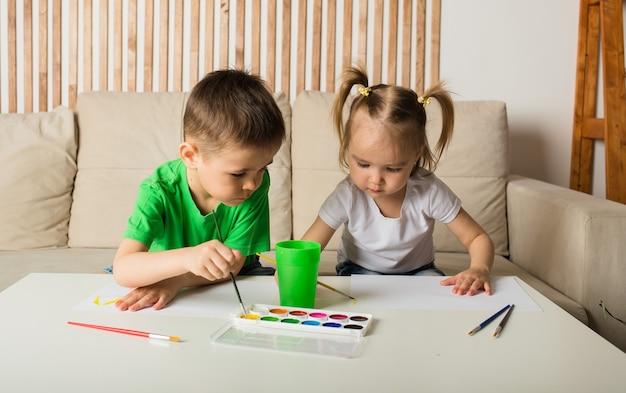 Um menino e uma menina desenham com pincéis e tintas em papel em uma sala
