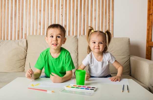 Um menino e uma menina desenham com pincéis e tintas no papel e olham para a câmera na sala