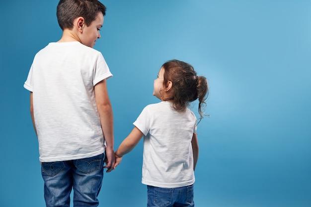 Um menino e uma menina estão de costas para a frente em uma superfície azul e se olham de mãos dadas