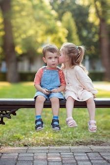 Um menino e uma menina estão sentados em um banco no parque uma menina beija um menino na bochecha