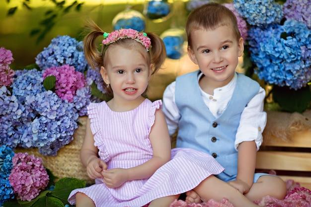 Um menino e uma menina estão sentados na grama na natureza com buquês de flores de hortênsia. irmão e irmã abraçam e riem