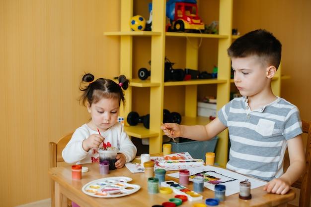 Um menino e uma mulher brincam juntos e pintam. entretenimento recreacional. ficar em casa.