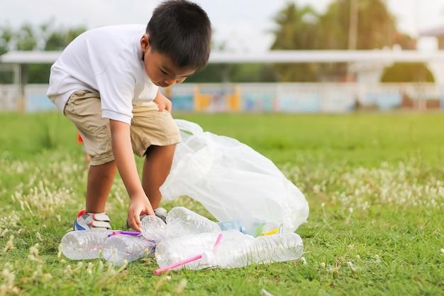 Um menino é voluntário para limpar o chão do campo. ele pegou muitas garrafas de plástico e palha no chão.