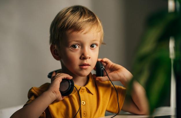 Um menino em idade escolar com uma camiseta amarela está sentado em frente a um computador e olha para o porta-retratos