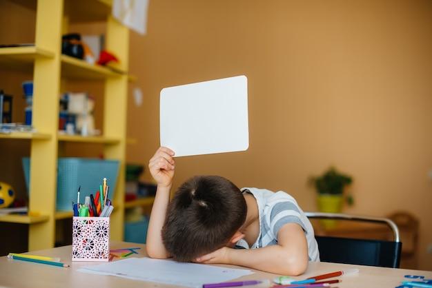 Um menino em idade escolar faz a lição de casa em casa. treinamento na escola.