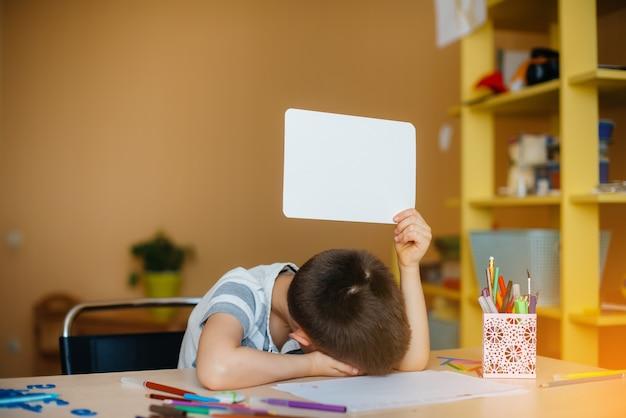 Um menino em idade escolar faz lição de casa em casa
