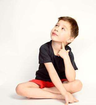 Um menino em um fundo branco. menino bonito sorridente sentado sobre um fundo branco.