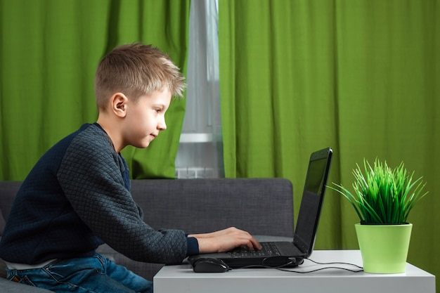Um menino em um laptop joga jogos ou assiste um vídeo