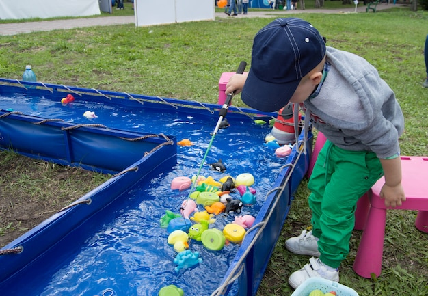 Um menino em um parque de diversões pega com entusiasmo